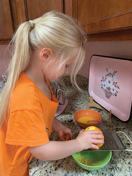 Blond haired girl child grating orange zest