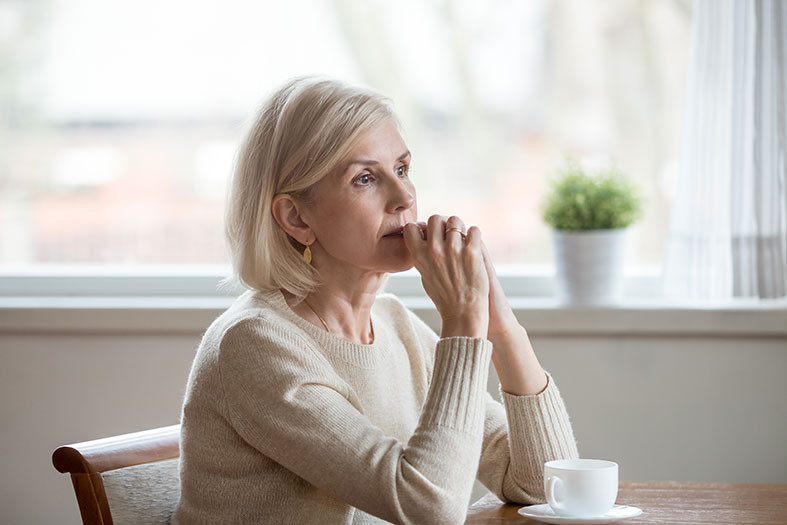older woman sitting at a table thinking