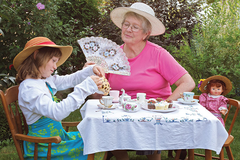 Grandmother and granddaughter having high tea outside