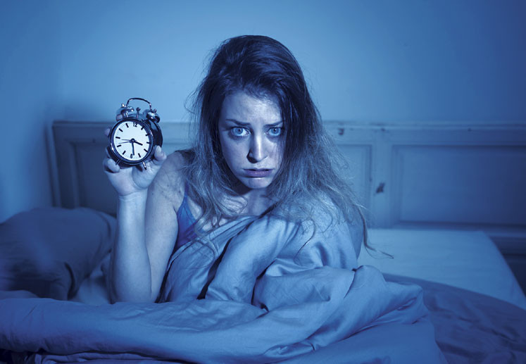 Woman sitting up in bed holding a clock and wants to sleep