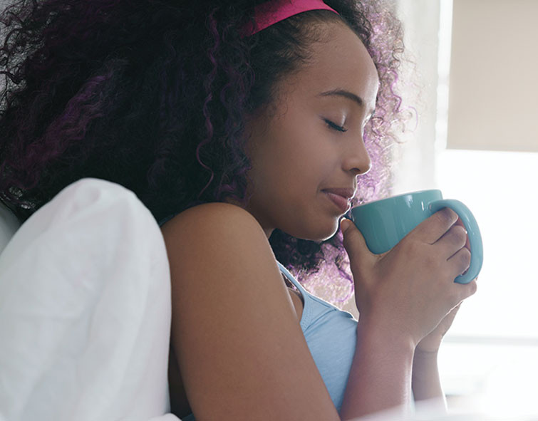 young black woman sipping a cup of tea