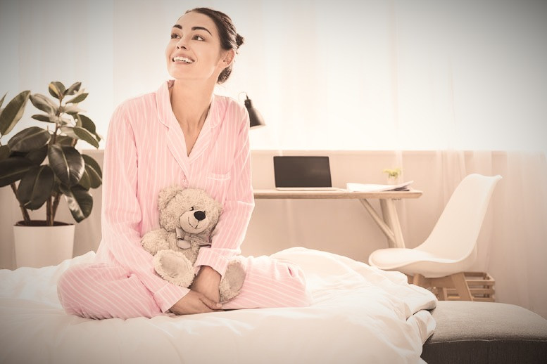 woman wearing pajamas sitting in bed holding a stuffed animal