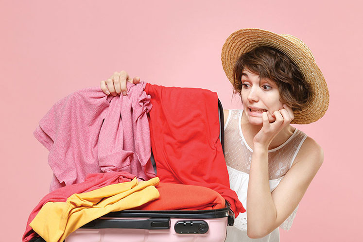 young woman stressing about packing her clothes properly