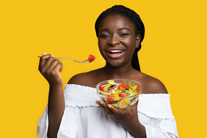 young woman smiles as she eats a bowl of fruit salad