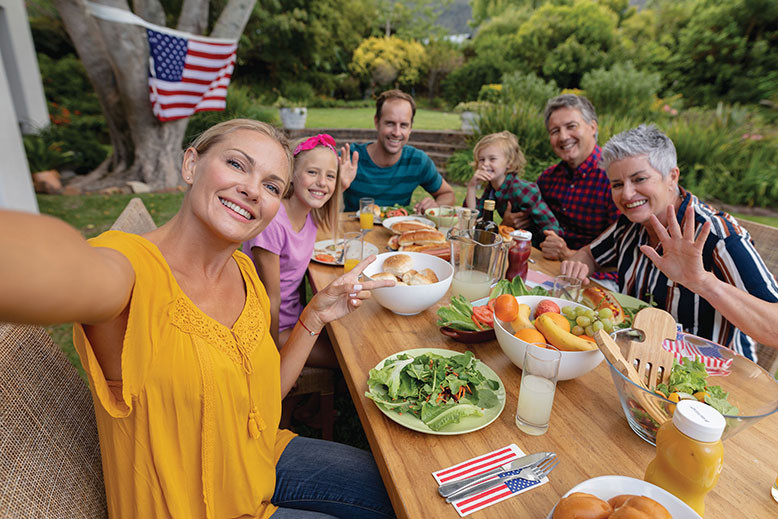 family of white people gathered to eat as a table outside