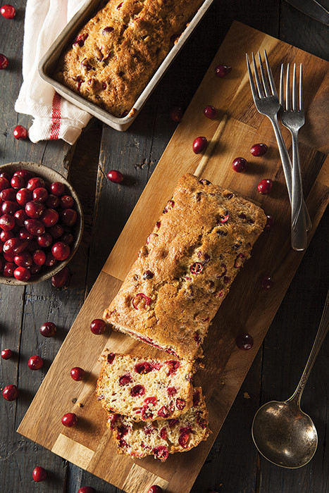 Looking down on two loaves of cranberry bread and cranberries