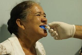 Dona Maria Marlúcia recebendo aplicação de flúor