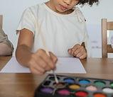 Child dipping brush in paint.jpg