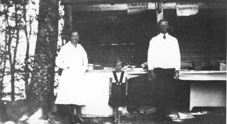 Det gamle slikhus i Floes Skov 1937. Her bestyret af Dagmar og Niels Rasmussen. Den lille pige er Anna Staach.