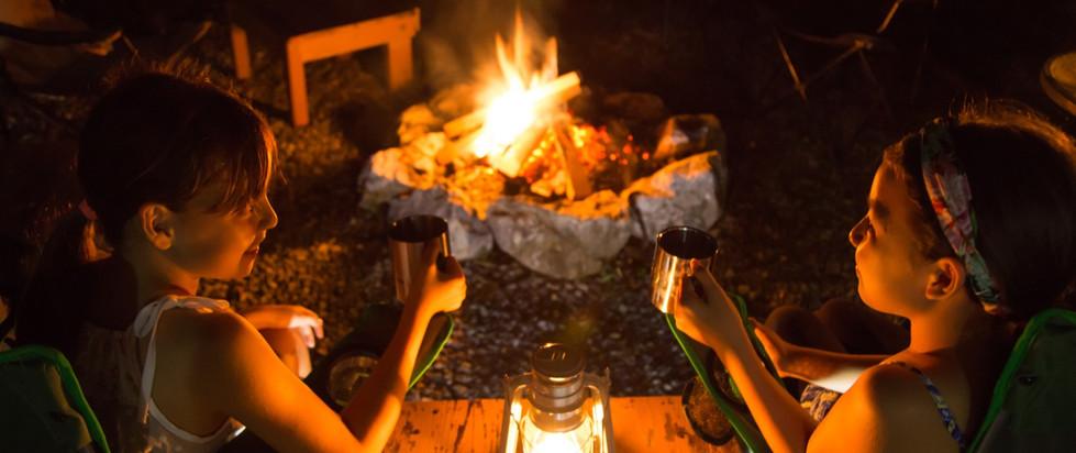 sitting around a campfire at phumula oki