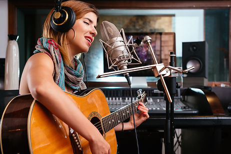 Young woman with guitar recording a song