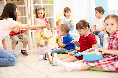 Teacher and cute children during music l