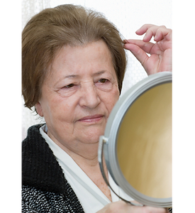 Picture of an older woman looking in a mirror and pulling on a single hair on her head.