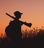 Silhouette of a sniper carrying a rifle