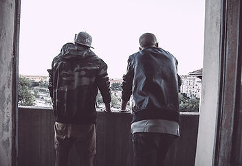 Picture of two men as seen from behind looking over a ledge at the city