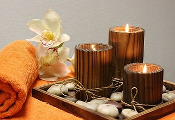 A serene and peaceful image of candles, stones, and a towel