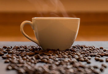 Picture of scattered coffee beans in front of a steaming cup of coffee
