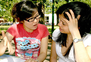 Picture of two teenage girls having an argument; one appears rejected