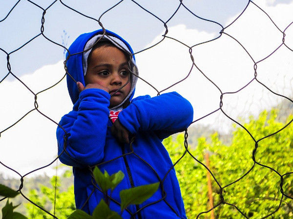Image of child behind a chain link fence.