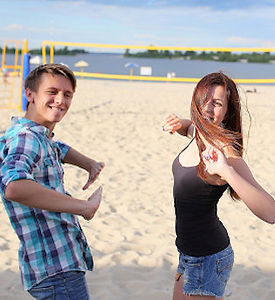Two young people dancing on the beach. They look somewhat awkward, but are smiling and having fun anyway.