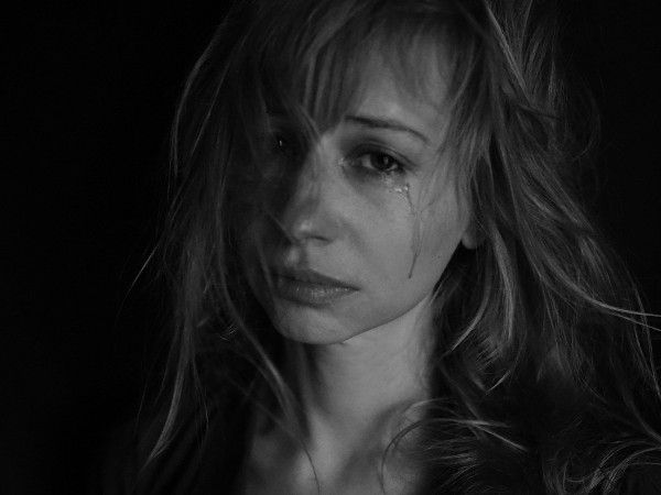 Image of a woman with frazzled hair and a single tear.