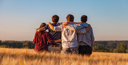 Four people with their arms around each other