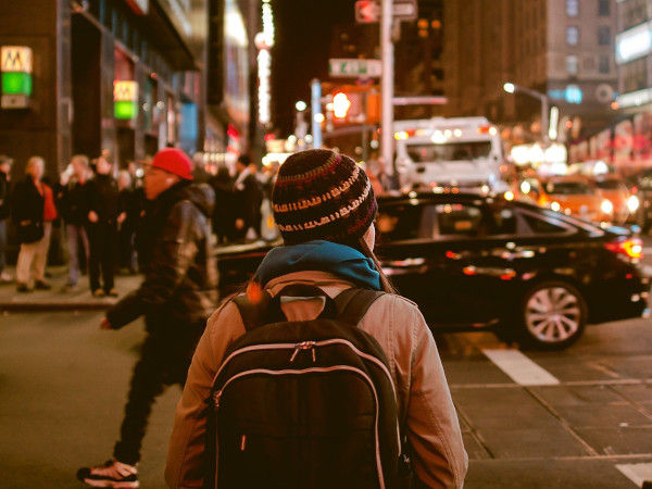 Image of a sole individual walking through a busy city.