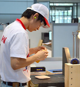 Picture of a man diligently working on a piece of wood