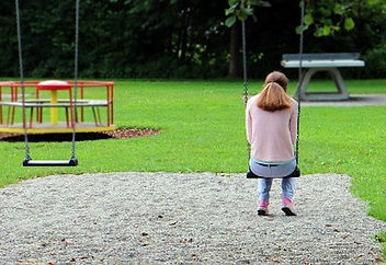 Picture of a woman sitting on a park swing alone