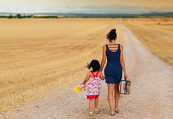 Picture of a woman and young girl walking down a long dirt road.