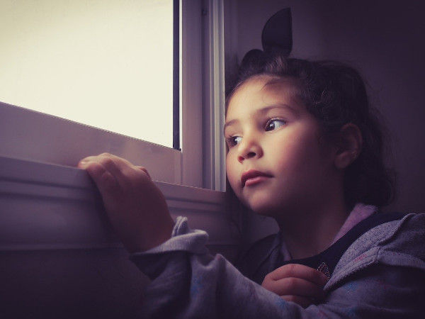 Image of a child peering through a window.