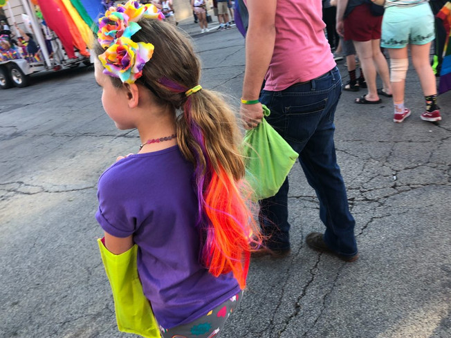 A young girl walks alongside many other participants of the Pride Parade in downtown Champaign, Illinois during Urbana-Champaign's 9th annual Pride Parade. People of all ages showed their support for the LGBTQ+ community by walking in the parade and sporting the rainbow colors of the pride flag.