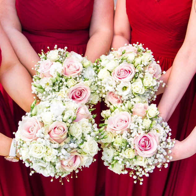 Bridesmaids holding flowers in red dresses