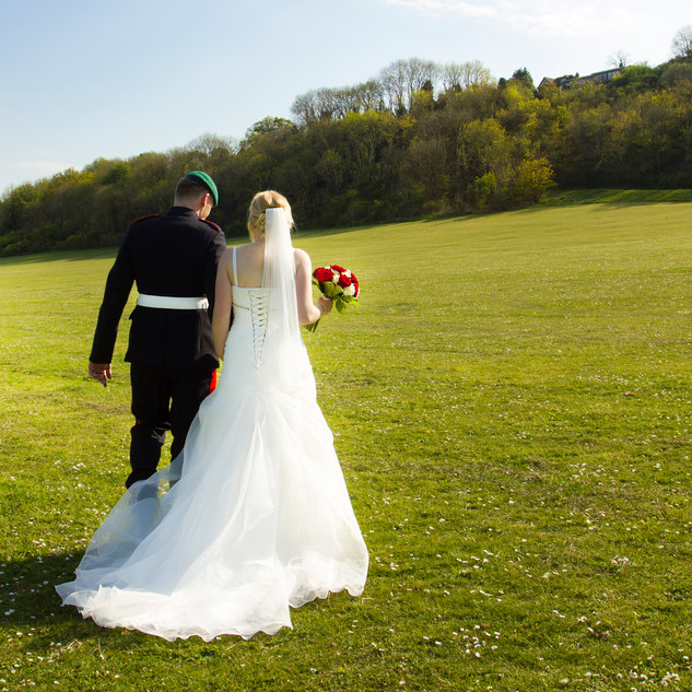Landscape bride and groom walking on the south downs in white wedding dress holding red roses
