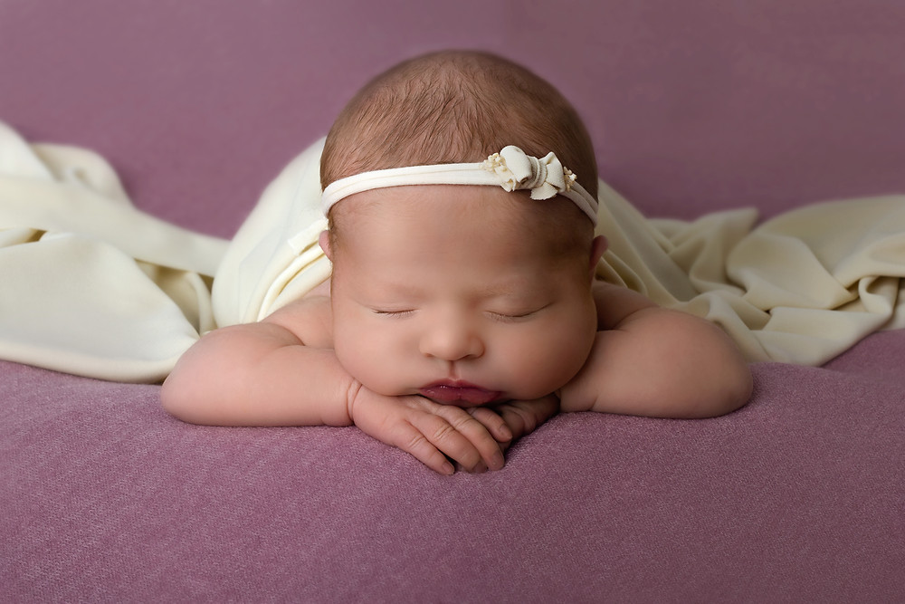 Newborn baby on pink background posing headband