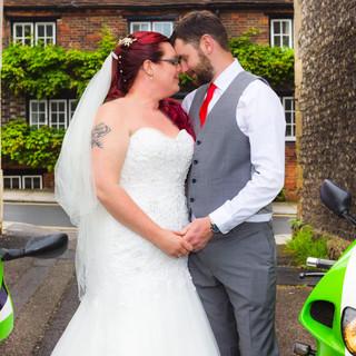 Bride and groom in-between two green kawazaki ninja's on wedding day