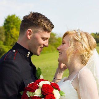 Mr and mrs Wedding day couple photoshoot holding red roses and army uniform