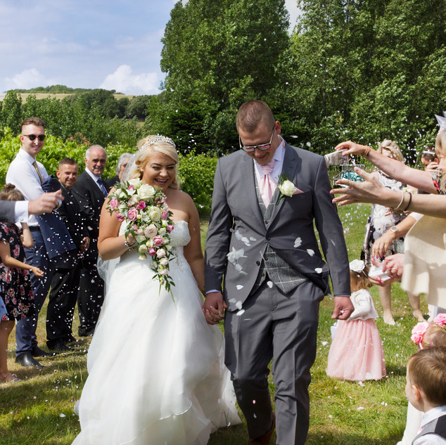 Bride and groom confetti throwing with family on south downs landscape