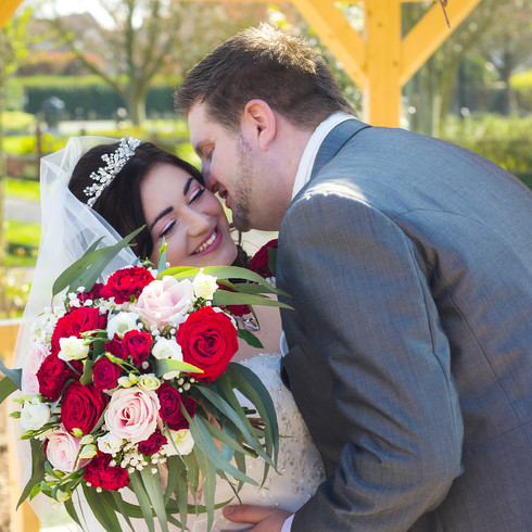 Bride and Groom with red and pink roses outside wedding | Panda Creative