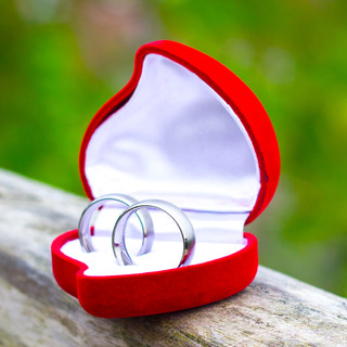 Close up of Bride and Groom silver wedding rings in red heart shaped box