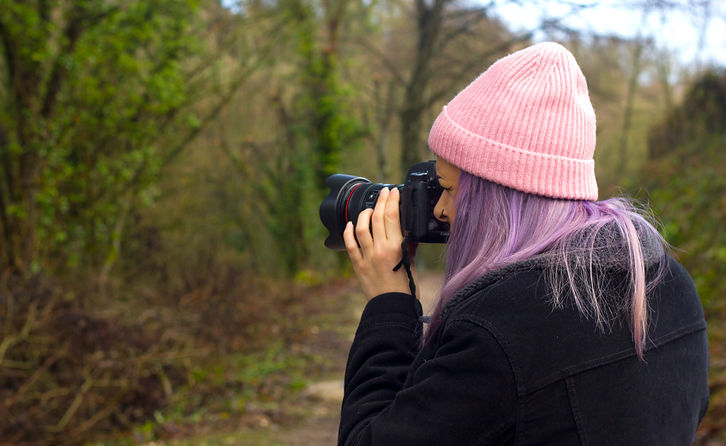 Photographer using Canon Camera in woodland
