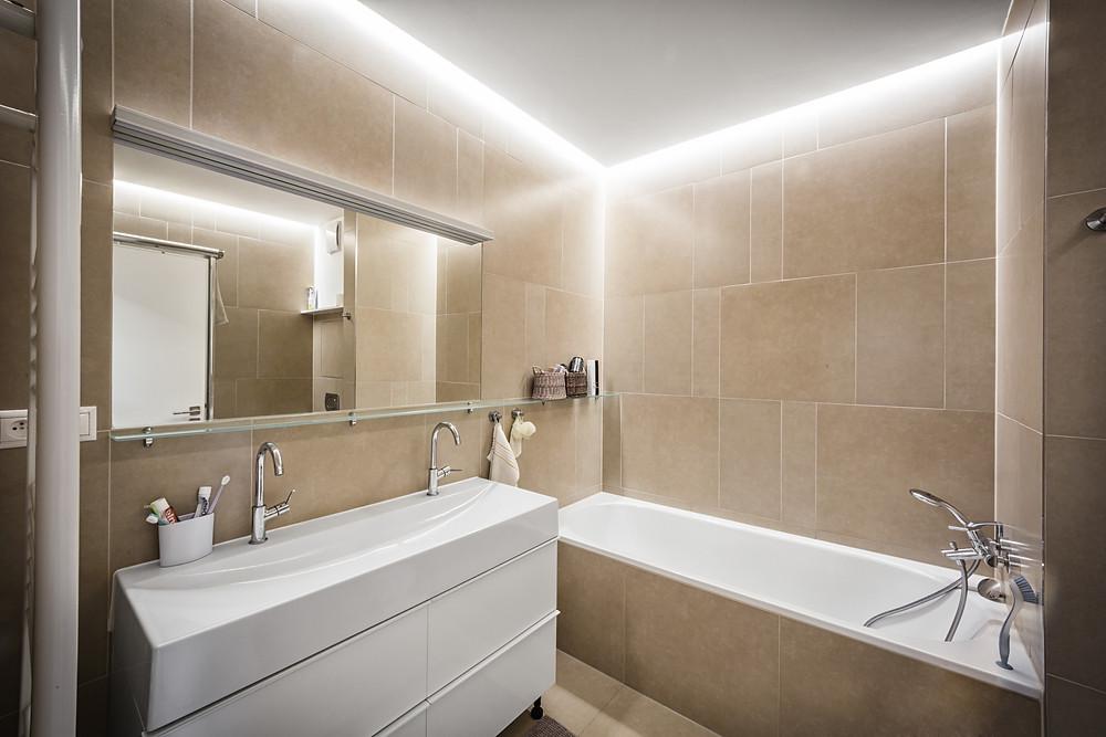 Lineárne osvetlenie kúpeľne pomocou štrbiny nad vaňou.