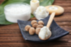 Plate with shea butter in wooden spoon and nuts on table.jpg