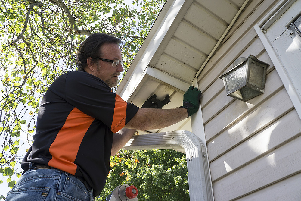 contractor installing vinyl siding and soffit on a home