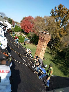 Roofers in harnesses installing felt underlayment on steep slope roof