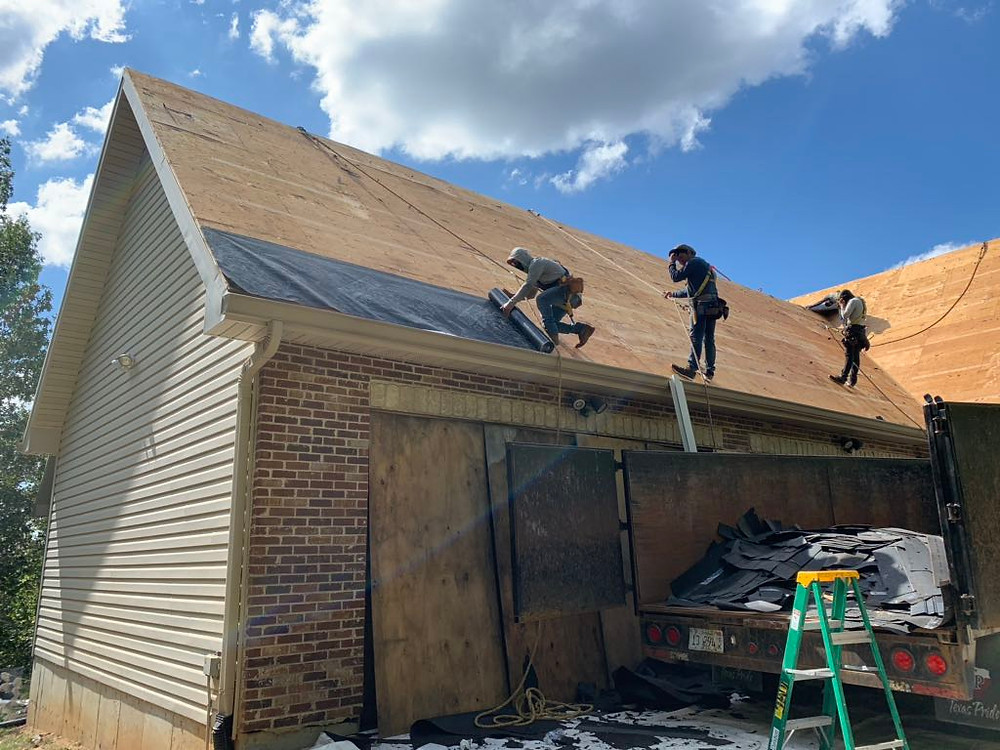 Contractors installing ice and water shield on a residential roof