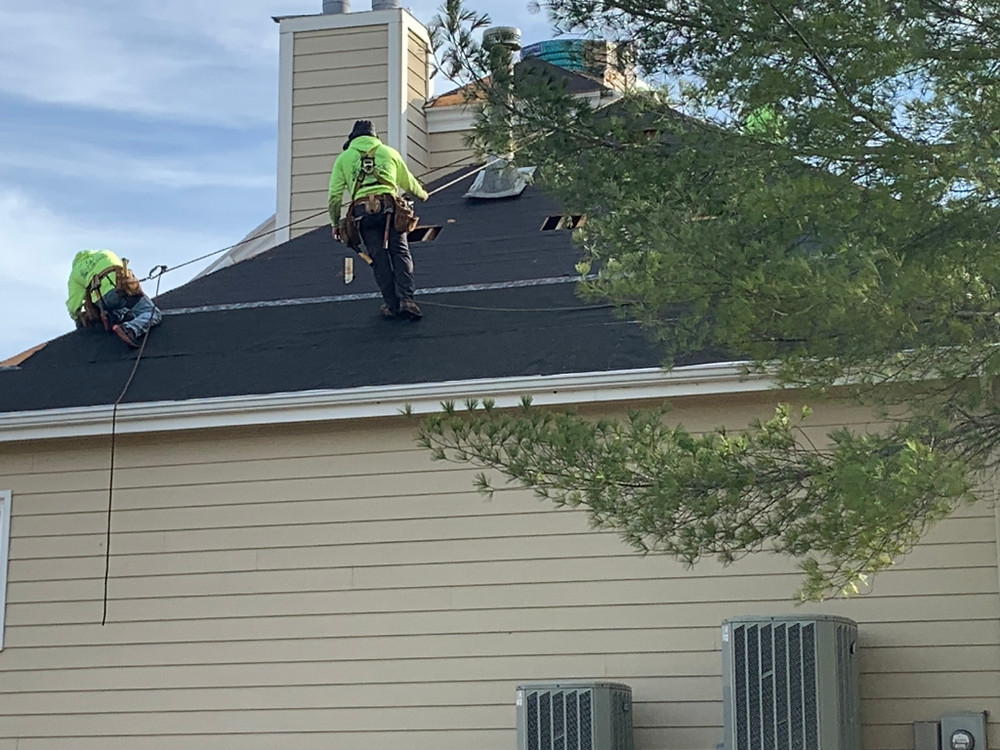 Roofing contractors in harnesses installing felt underlayment on a roof
