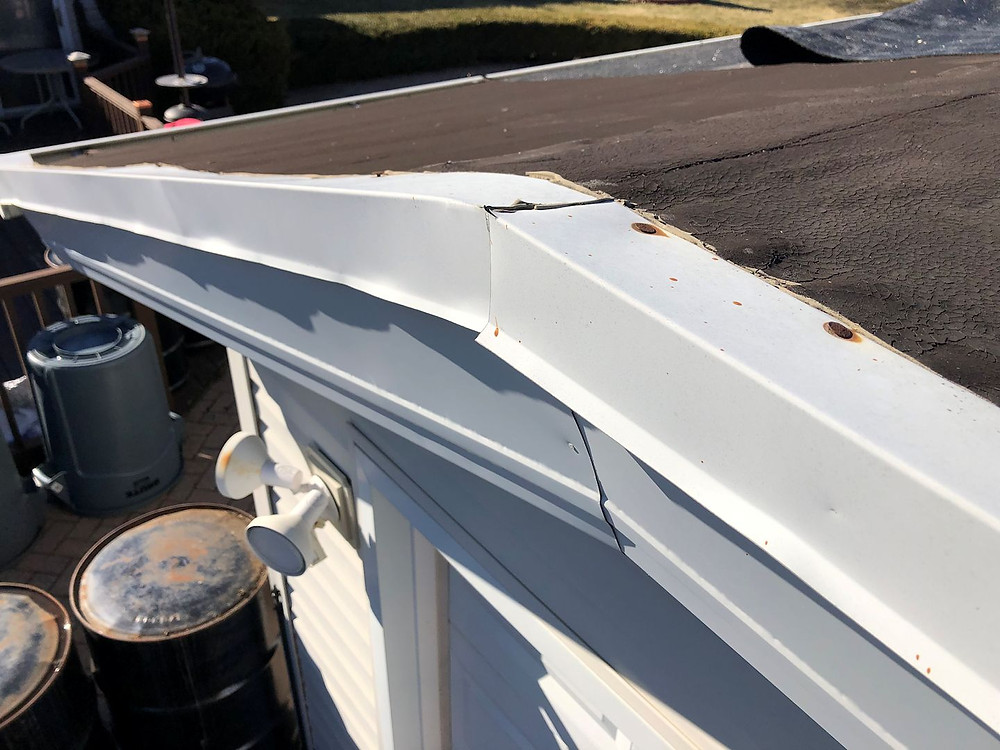White drip edge on residential roof that has been damaged in a storm
