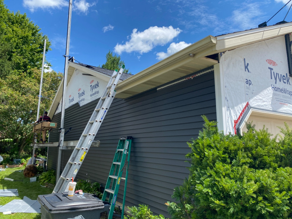 contractor using ladder jack scaffolding during a vinyl siding install