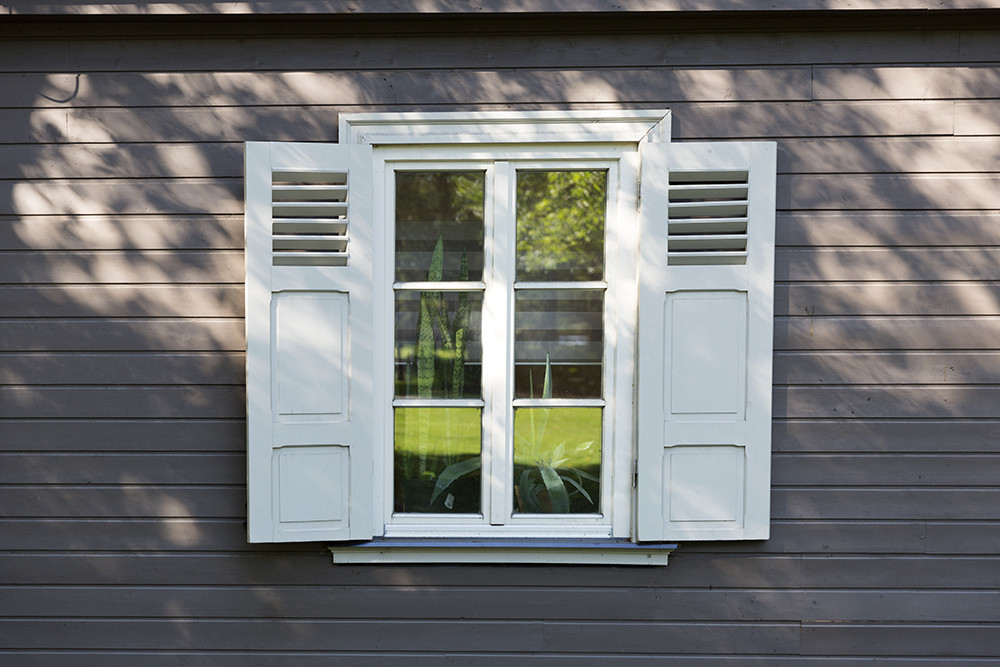 White wooden shutters on 2nd story window